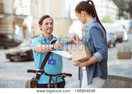 Sign it here. Positive delighted professional courier using a bicycle and holding folder while the client putting a signature