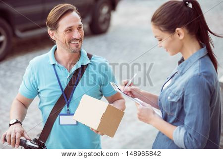 Like my work. Positive bearded professional courier holding the parcel and delivering it while smiling client signing the paper