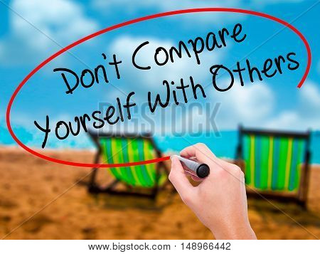 Man Hand Writing Don't Compare Yourself With Others With Black Marker On Visual Screen