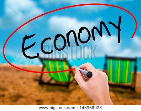 Man Hand Writing Economy With Black Marker On Visual Screen.