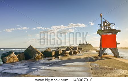 View at Nobbys lighthouse and Nobbys Breakwall during daytime with blue skies and white clouds