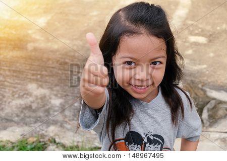 Portrait of cute little girl thump up