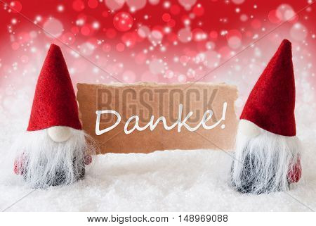 Christmas Greeting Card With Two Red Gnomes. Sparkling Bokeh And Christmassy Background With Snow. German Text Danke Means Thank You