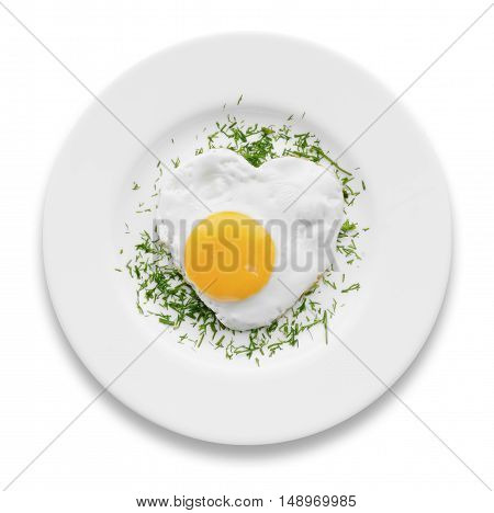 Heart-shaped fried egg with herbs on a white plate isolated
