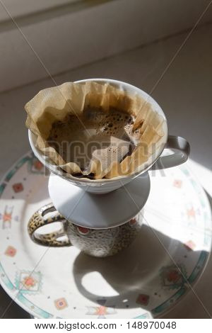Manually brewing pour over coffee showing a close up of a mug with a pour over dripper and paper filter holding coffee on top with water dripping down through the coffee grounds into the mug below