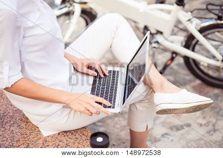 Computerized world. Pleasant woman using laptop and sitting in the street