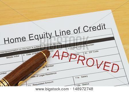 Applying for a Home Equity Line of Credit Approved Home Equity Line of Credit application form with a pen on a desk with an approved stamp