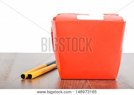 Chinese take away red food box with chopsticks on thetable isolated on white