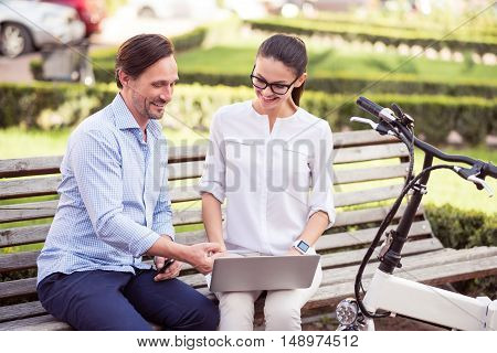 Modern city dwellers. Positive content friends smiling and using laptop while sitting on the bench