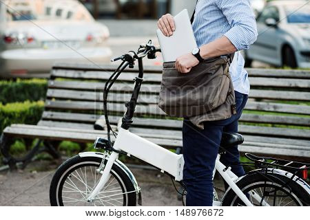 Pleasant ride. Handsome sportive man holding laptop and putting it into the bag while sitting on the bike.