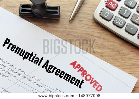 Approved prenuptial agreement lay down on wooden desk with rubber stamp and calculator.