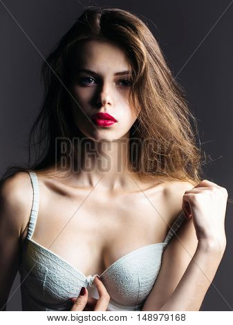 young sexy fashionable woman or girl with long brunette hair and red lips on pretty face in white erotic lingerie in studio on grey background