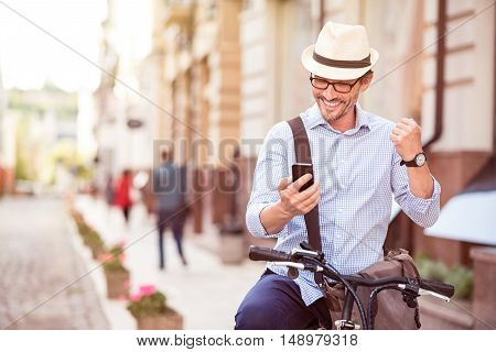 Full of emotions. Cheerful handsome adult man using cell phone and standing with his bicycle in the street while resting
