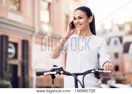 Quick tempo of life. Positive delighted beautiful woman talking on cell phone and riding a bicycle