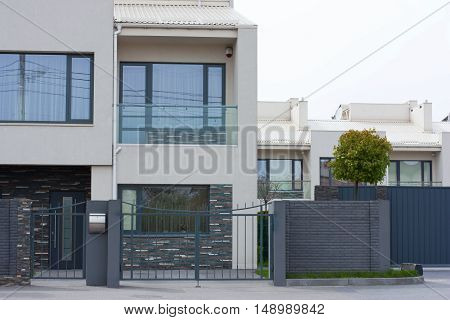 Cottage house behind the fence. Modern exterior of home.Modern stylish facade