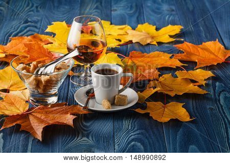 Autumn evening with coffee and cognac on blue background