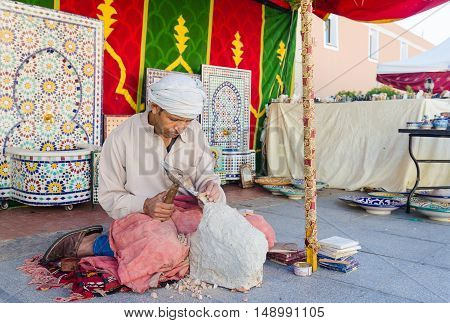 Badajoz Spain - September 23 2016: Sculptor arabic man working sculpting sculpture in market during celebration of Almossassa Badajoz Extremadura spain