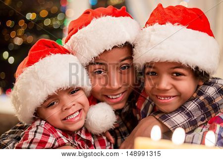 Three kids in Christmas hats. Smiling afro boys on Christmas. Three happy brothers on holidays. Christmas evening at family house.