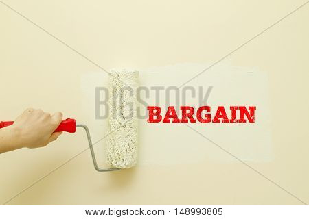 Woman hand painting wall written Bargain word on it.