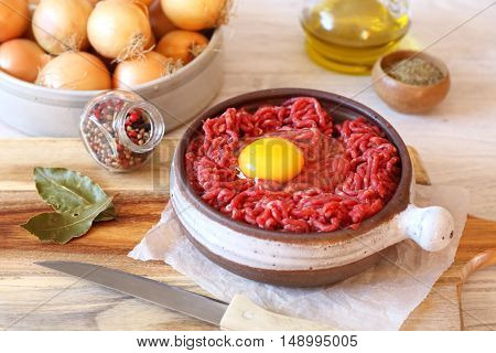 Raw minced meat with egg in ceramic pot olive oil seasoning and onions
