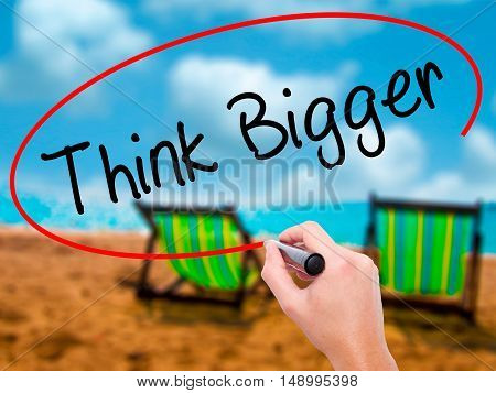 Man Hand Writing Think Bigger With Black Marker On Visual Screen.