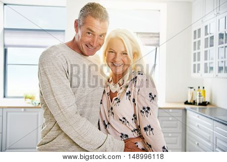 Happy middle aged handsome husband hugging beautiful wife at kitchen counter while standing together