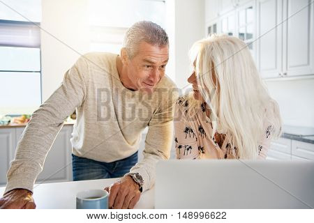 Curious middle aged couple looking at computer on kitchen counter with excited or celebratory expression
