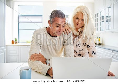 Bright kitchen scene with attractive senior couple looking at something interesting on their open laptop computer together