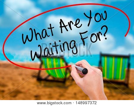 Man Hand Writing What Are You Waiting For?  With Black Marker On Visual Screen