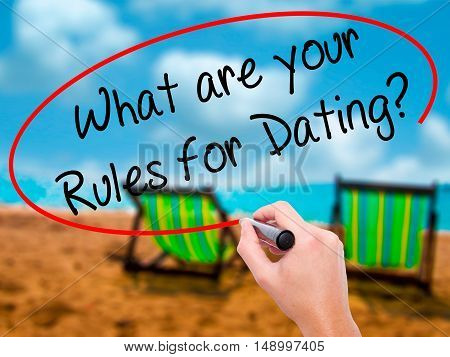 Man Hand Writing What Are Your Rules For Dating?  With Black Marker On Visual Screen