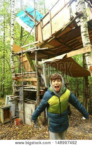 preteen boy in the autumn forest self made hut close up photo
