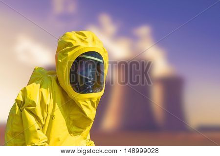 View of smoking coal power plant and men in protective hazmat suit