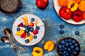 Detox and healthy superfoods breakfast bowl concept. Vegan coconut milk chia seeds pudding over blue stone table with various fruits and blueberries. Overhead top view flat lay. poster