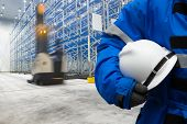 Worker in uniform with safety hardhat for dangerous accident protection in warehouse during work poster