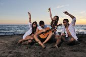 happy young friends group have fun and celebrate while jumping and running on the beach at the sunse