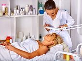 Woman middle-aged in spa salon with young beautician. Tweezing eyebrow by beautician in spa salon. poster