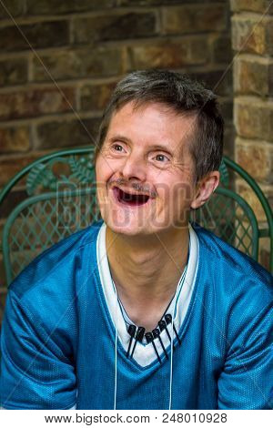An Older Man With Downs Syndrome Gives A Huge Smile.  The Delight On His Face Shows Off The Fact Tha