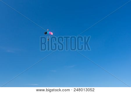 Blue Sky And Colorful Parachute Carrying Lonely Human To The Earth