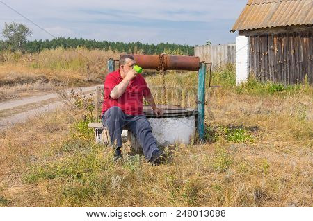 Senior Man Drinking Water Sitting On A Bench Near An Old Draw-well In Rural Village In Poltavskaya O