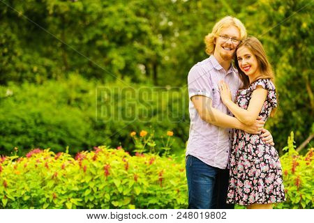 Happy Joyful Teen Couple Hugging Outdoor In Green Park During Beautiful Summer Weather.