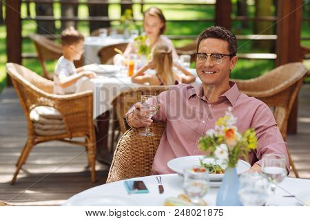Looking At Wife. Pleasant Handsome Man Looking At His Lovely Beautiful Wife While Sitting In Restaur