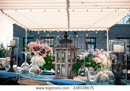 Romantic Wedding Or Another Catered Event Table Setting, Flowers, White Plates, Blue Napkins, White