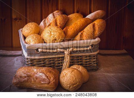 Fresh Wheat Bread In Wicker Basket And Near On Wooden Table