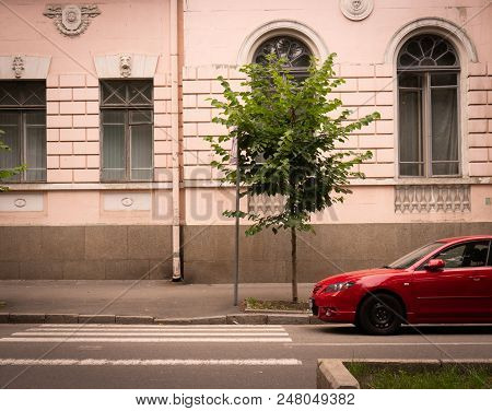 Red Sports Car On A City Street Background.