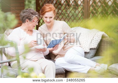 Young Nurse And An Elderly Woman Reading A Book Together On The Terrace Of A Nursing Home