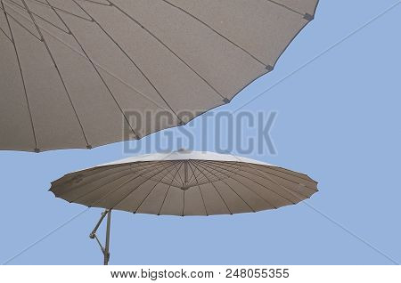 Parasols Giving Some Shade In Hot Sunshine In July In Mallorca, Spain.