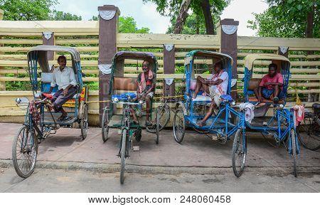 Bodhgaya, India - July 9, 2015. Rickshaw Drivers Waiting On Street In Bodhgaya, India. Bodhgaya Is T
