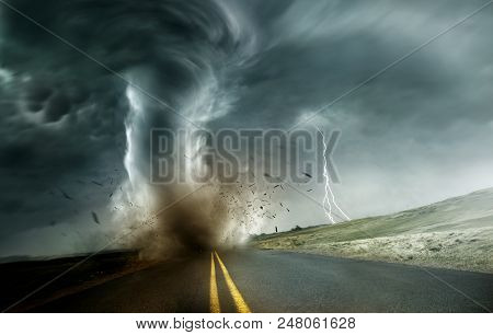 A Powerful And Dark Storm Producing A Tornado Crossing Through Fields And Roads. Dramatic Landscape