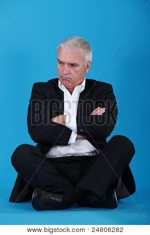 angry senior businessman sitting cross-legged