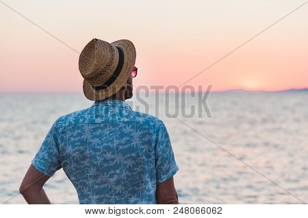 Young Man Enjoying Sunset By The Sea